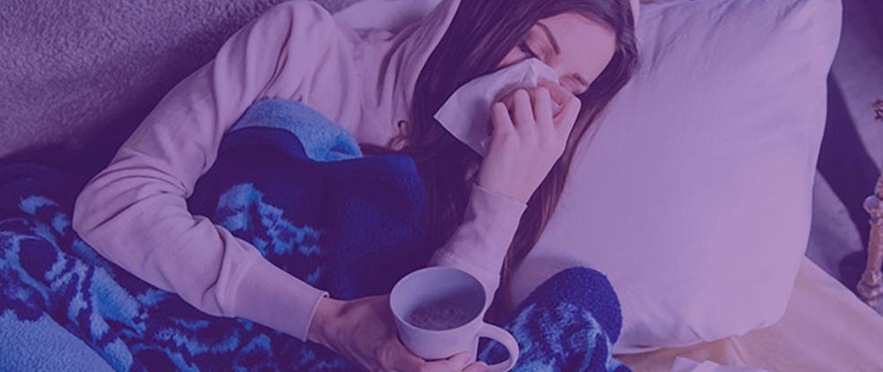 Jovem mulher gripada deitada sob cobertor na cama