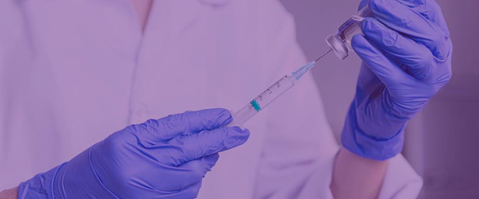 Médico com luvas colocando vacina na seringa