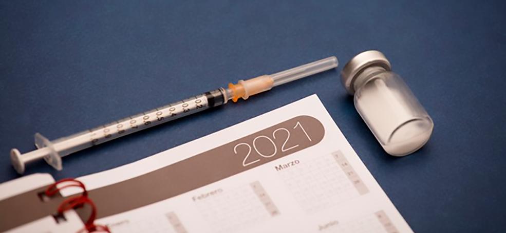 Calendário 2021 com seringa e recipiente de vacina em superfície azul